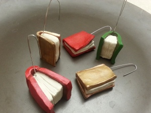 Book-shaped Christmas tree ornaments made from polymer clay as prizes for the Calgary Wrimotaurs.